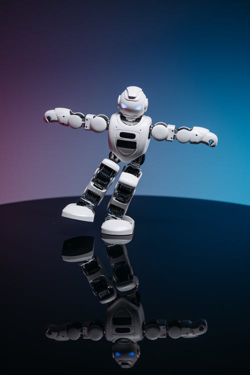 Close Up Shot of White Toy Robot on Blue and Pink Background
