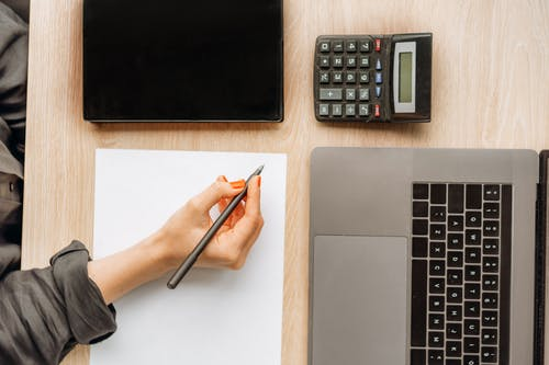 Person Holding a Pen on Top of a Desk