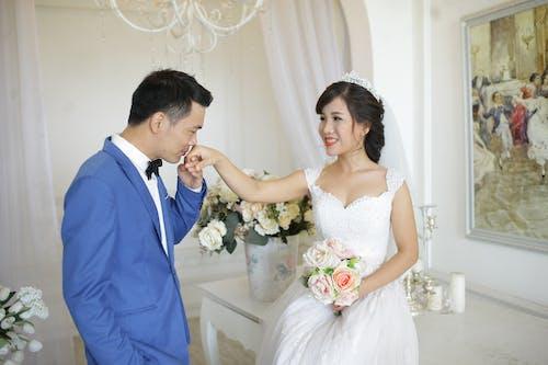 Man in Blue Suit Jacket Kissing Woman in White Wedding Dress