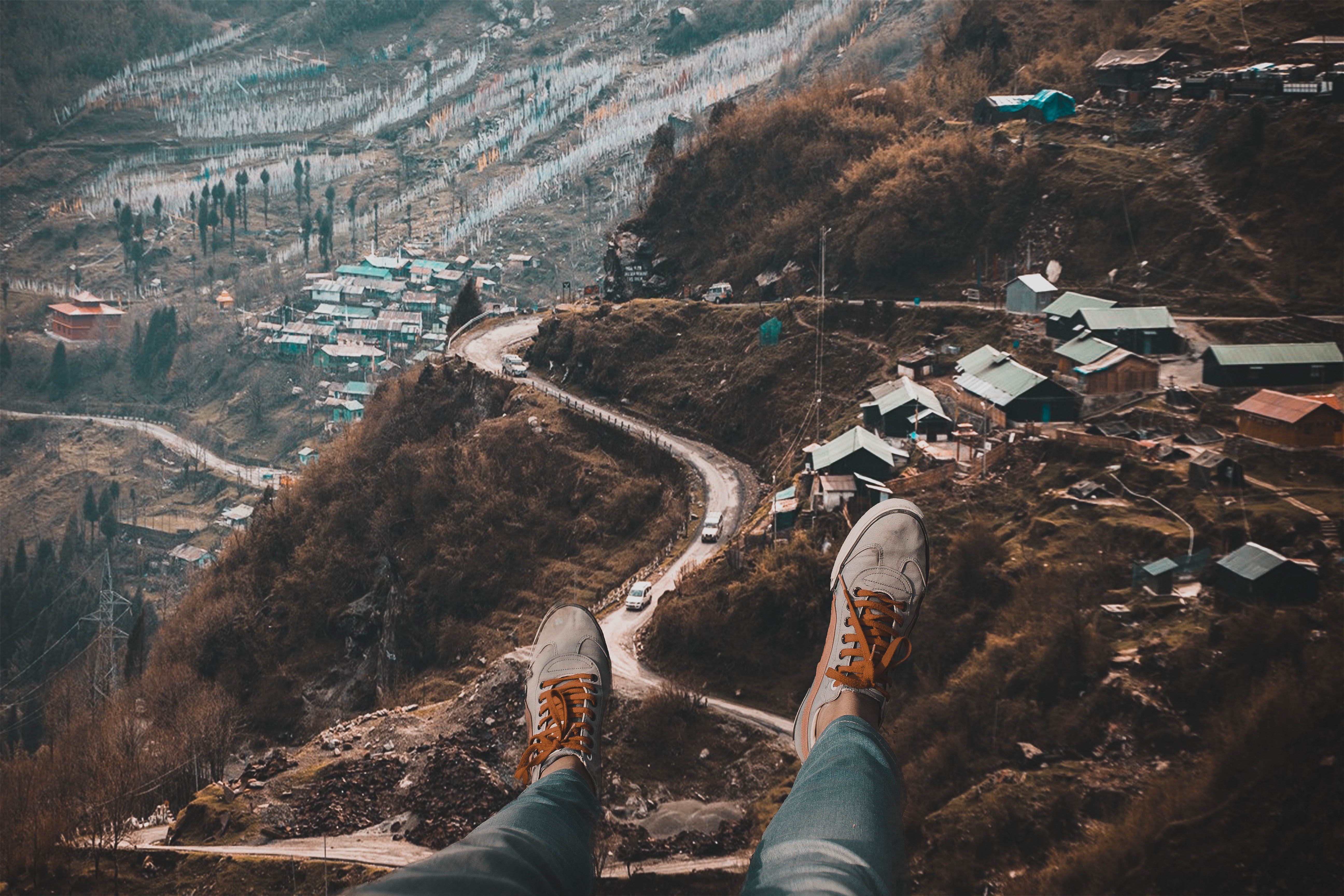 Person Wearing White Sneakers With Overlooking of Village on Hills