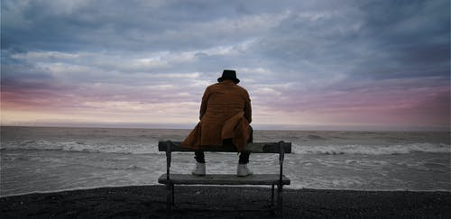 Person in Brown Jacket Sitting on Black Wooden Bench on Beach