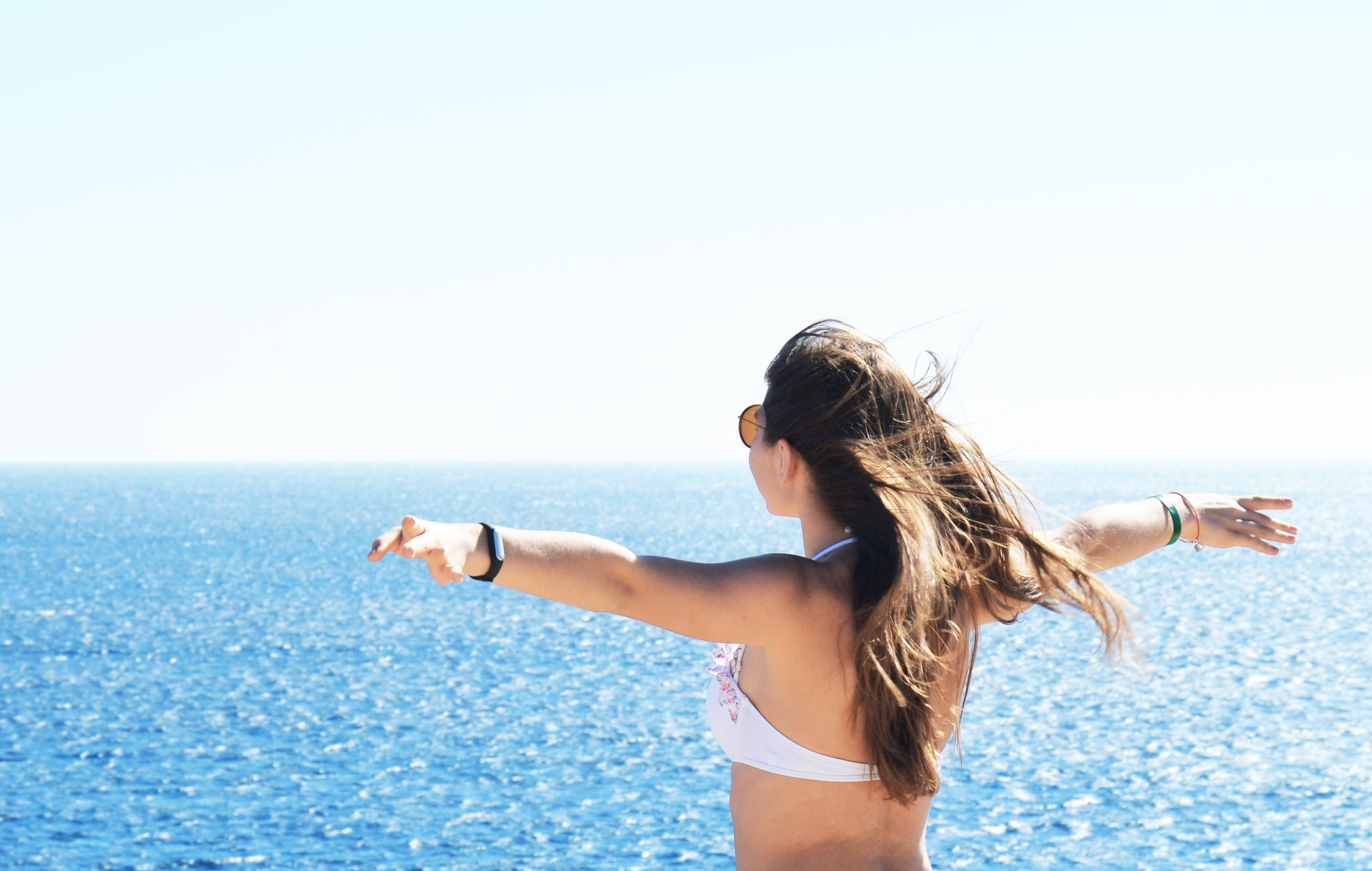 Woman Wearing White Bikini Top Standing Near Body of Water