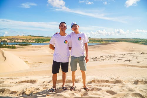 Man in Blue Polo Shirt Standing Beside Man in White Crew Neck T-shirt