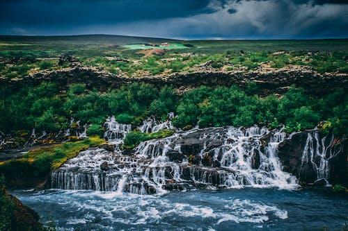 Kostenloses Stock Foto zu bäume, dramatischer himmel, island, kaskade