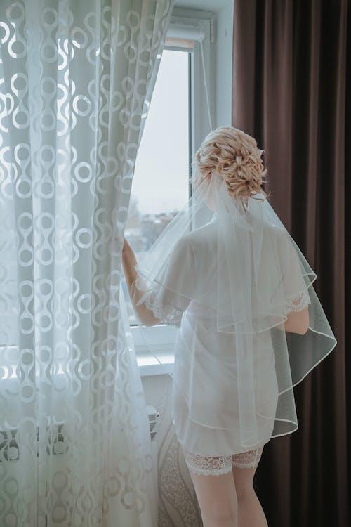 Woman in White Wedding Dress Standing Near Window