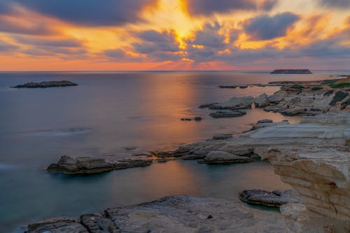 Shore with rough stones washed by calm sea against colorful sky with clouds at sundown time in nature on summer evening