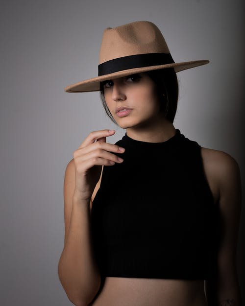Close-Up Shot of an Attractive Woman in Black Sleeveless Crop Top with Fedora Hat Looking at Camera