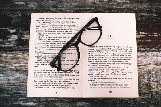 Photography of Eyeglasses on Top of Book