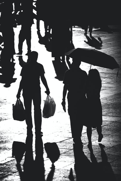 Grayscale Photo of Silhouette of People Walking on the Street