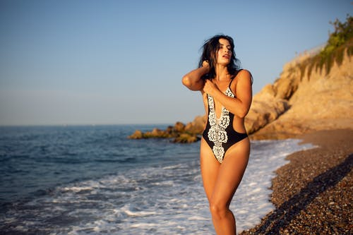 Woman in Black and White Floral Bikini Standing on Beach Shore