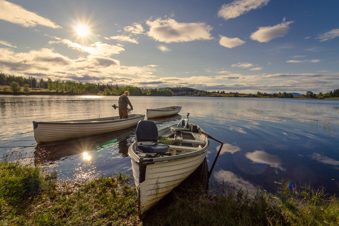 Fisherman on White Wooden Boat