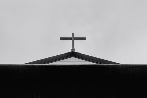 Cross on roof of church against sky