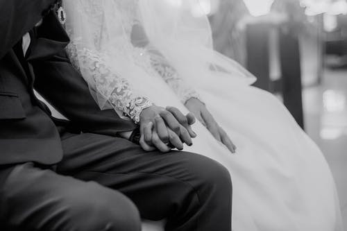 Newlywed couple in festive clothes sitting and holding hands