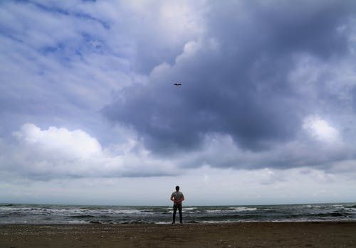 Woman in Black Jacket Standing on Beach Under Cloudy Sky