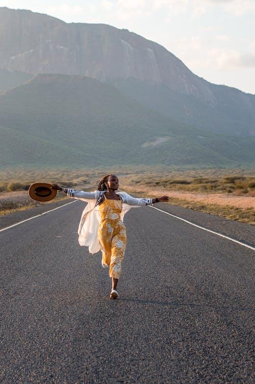 Woman in White Dress Holding Brown Hat Walking on Gray Asphalt Road