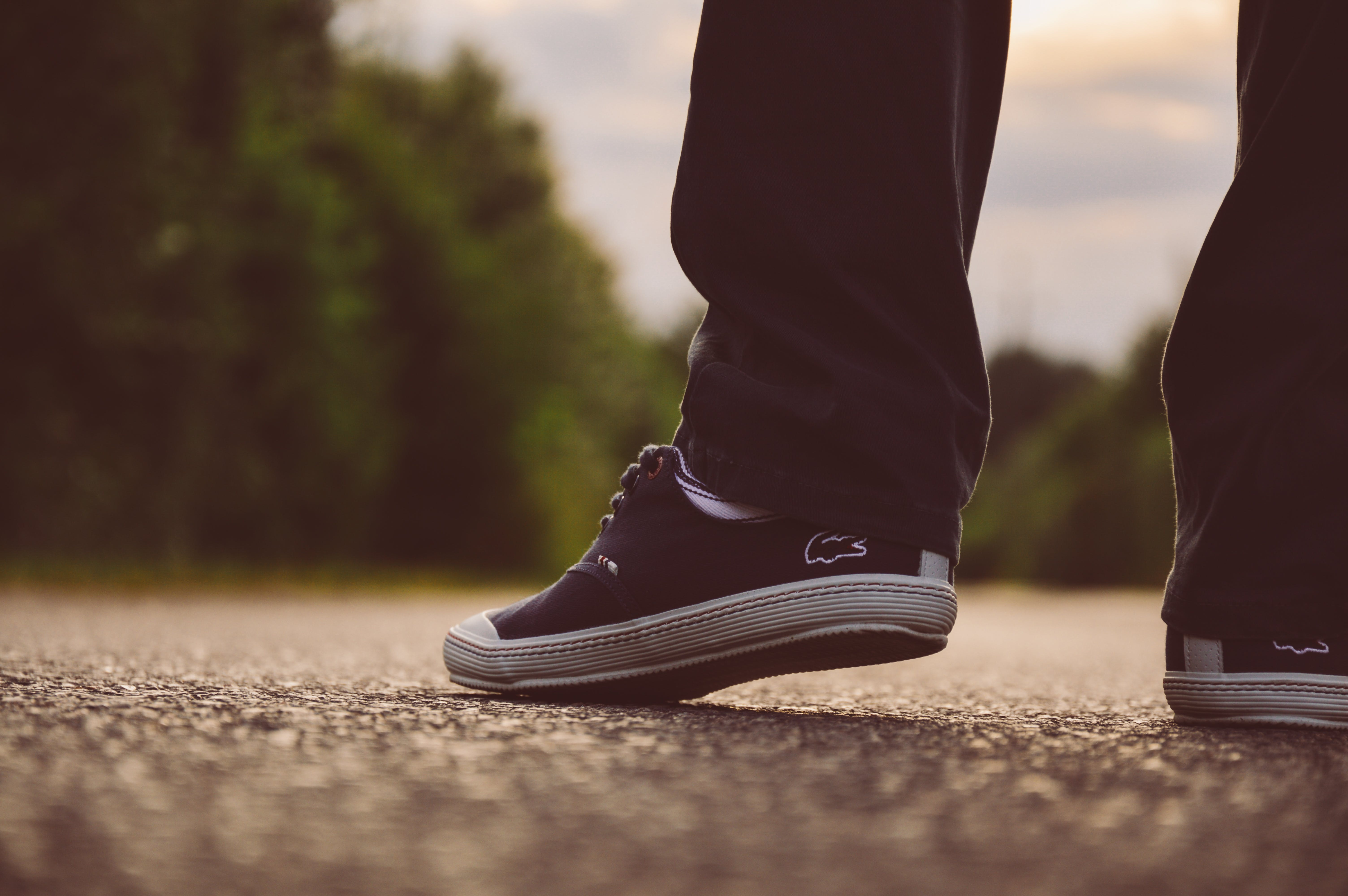 Person Wearing Black-and-white Lacoste Sneakers on Gray Concrete Road