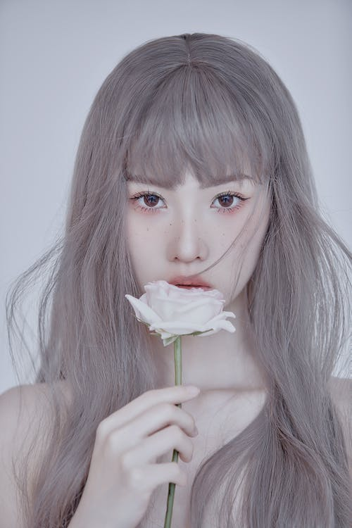 Close-Up Shot of a Pretty Woman with Gray Hair Looking at Camera while Holding a White Rose