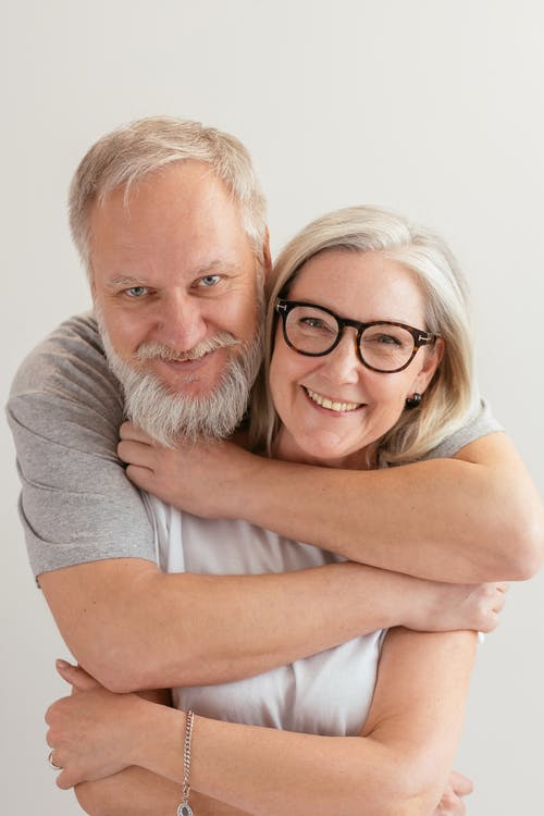 Close-Up Shot of a Happy Elderly Couple Hugging while Looking at Camera