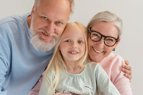 Close-Up Shot of a Happy Elderly Couple with Their Grandchild Hugging while Looking at Camera