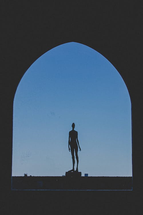 Silhouette of human statue on top of stairs in archway on background of blue sky in evening