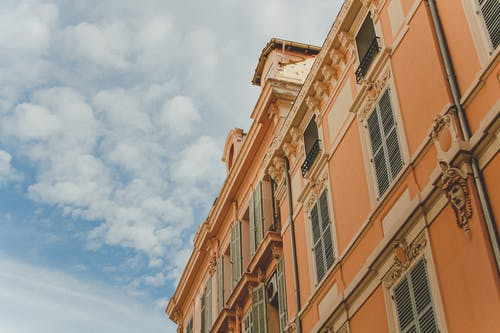 Facade of old building against cloudy blue sky