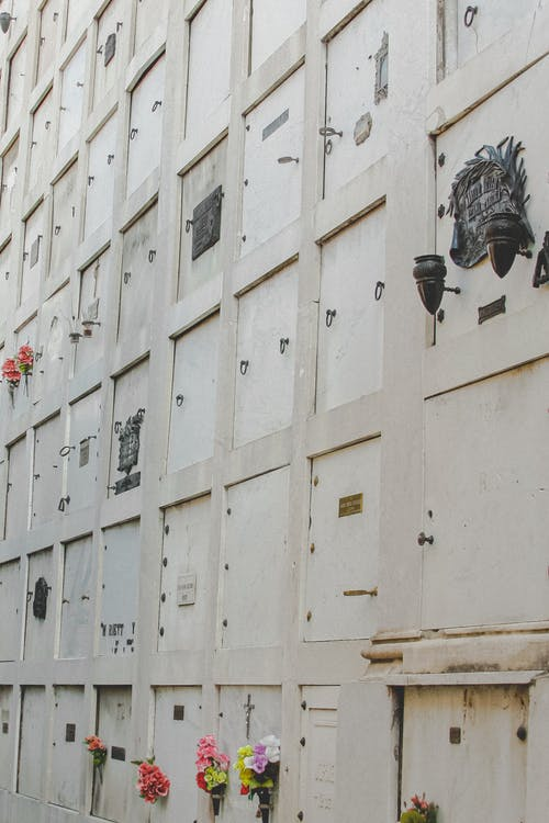Full frame view of columbarium wall of white stone color with flowers on cemetery