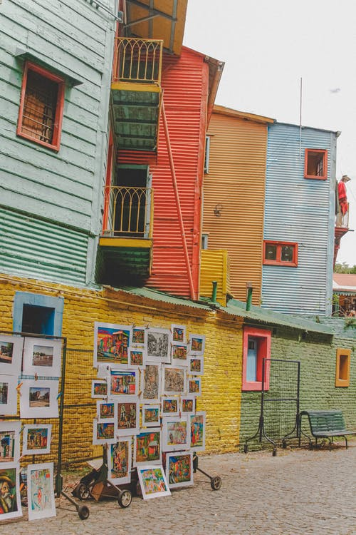 Facade of multicolored houses with painted pictures for selling on wall on street