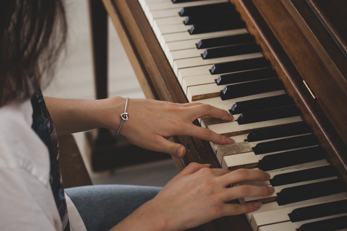 Person in Blue Denim Jeans and Silver Bracelet Playing Piano