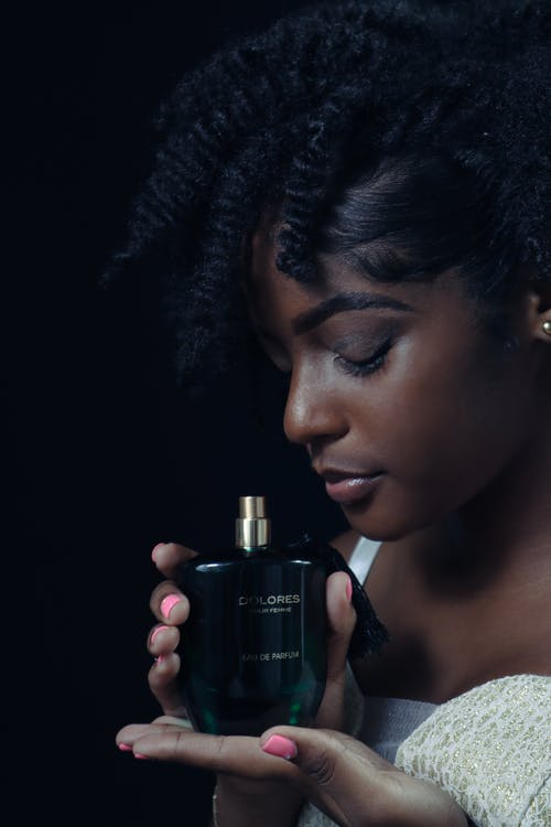 Close-Up Shot of an Afro-Haired Woman Holding a Perfume Bottle