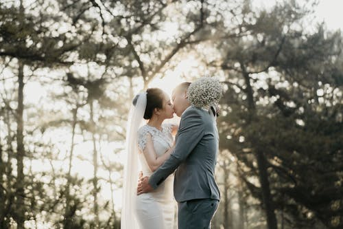 Man and Woman Kissing Under Green Tree