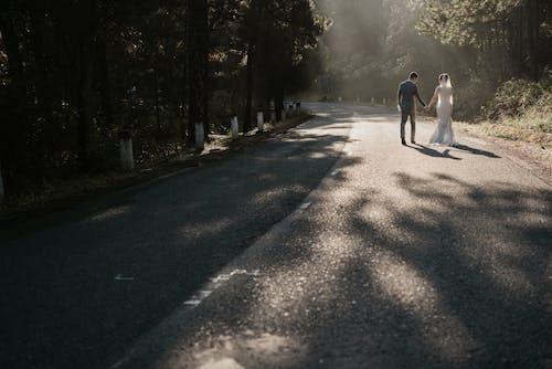 Man in White Shirt and Black Pants Walking on Gray Asphalt Road