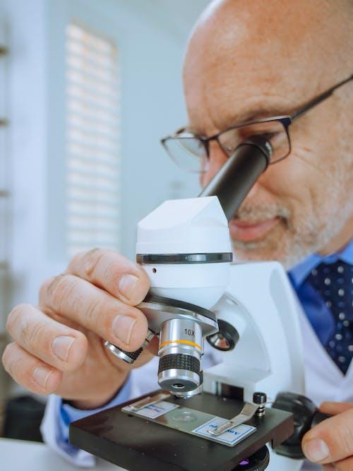 A Man Examining a Microscope Slide