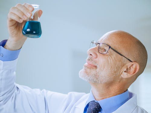 A Man in White Coat Doing an Experiment