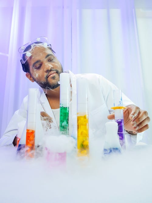 Man in White Coat Doing an Experiment