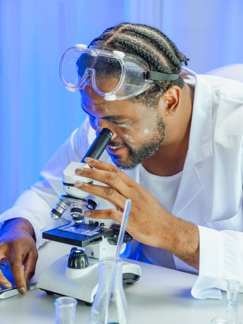 A Man Looking into the Microscope