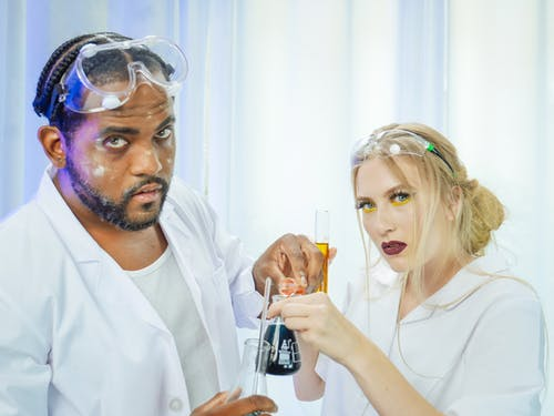Man and Woman in White Coat Doing an Experiment