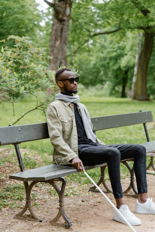 Man in Brown Coat Sitting on Bench
