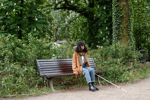 Woman in Brown Jacket Sitting on Brown Wooden Bench