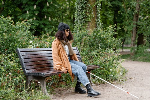 Woman in Brown Coat Sitting on Brown Wooden Bench