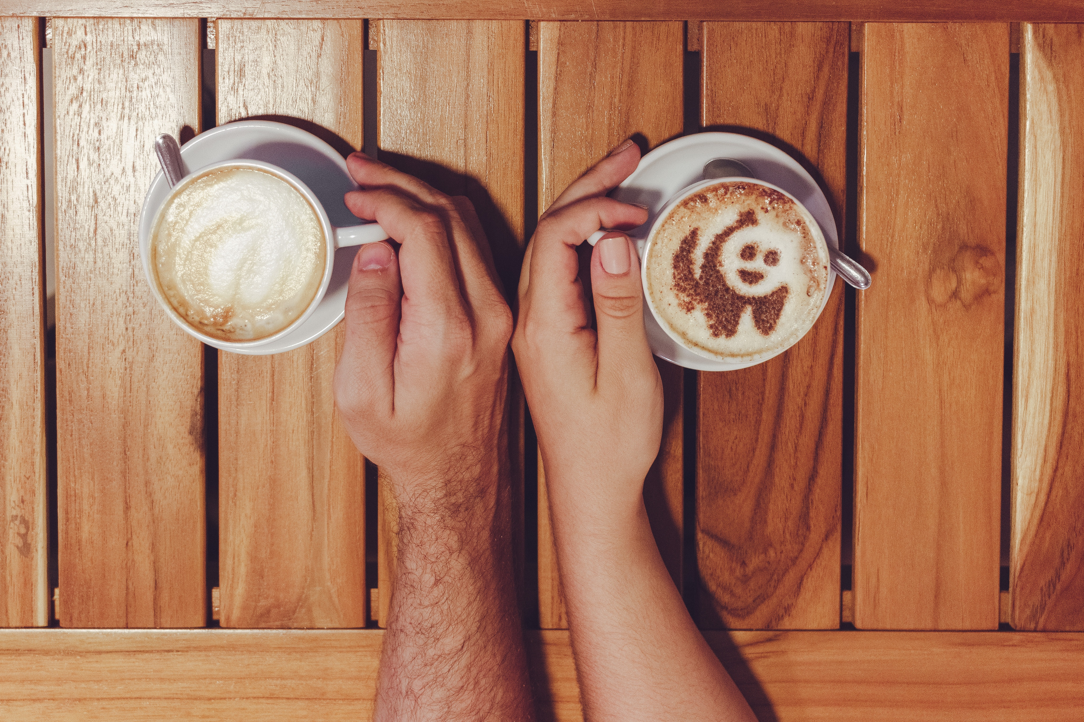 Person Holding Cup of Coffees on Table · Free Stock Photo
