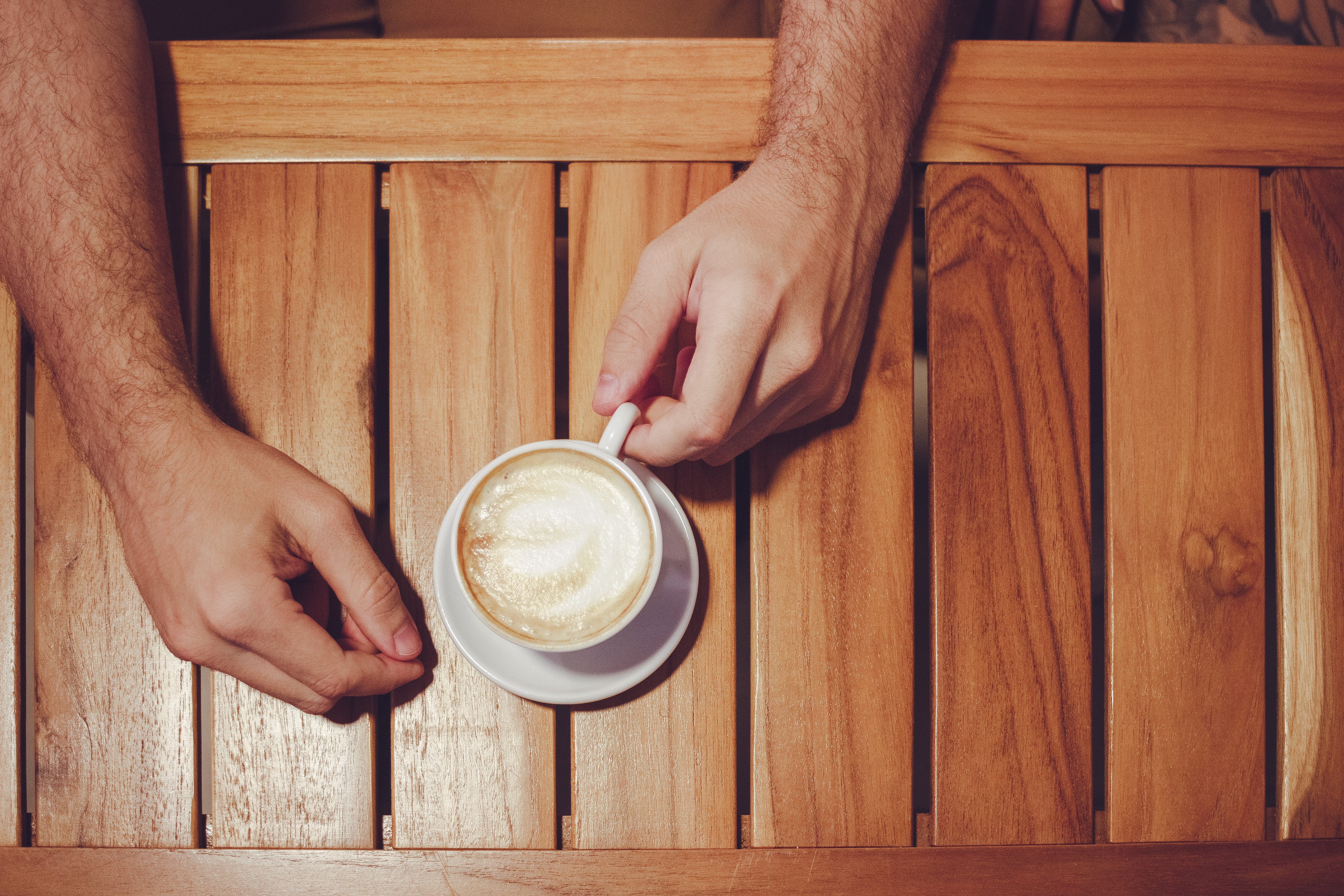 Person Holding White Ceramic Cup With Cappuccino on Brown Wooden Table