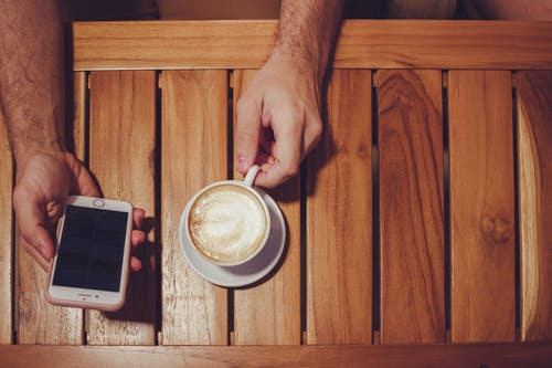 Person Holding Turned Off Gold Iphone 6 With Case and White Ceramic Cup Filled With Latte