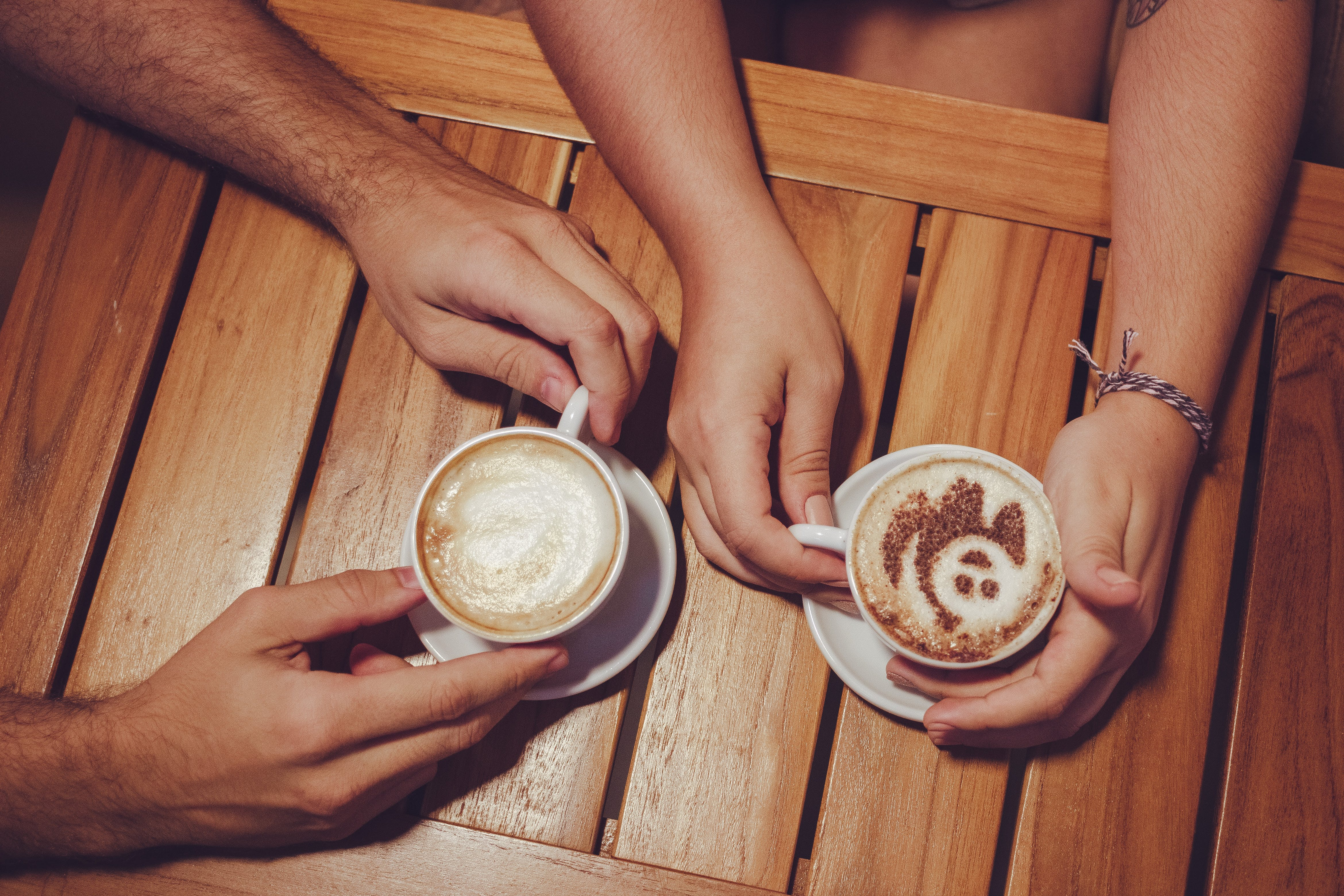 Two People Holding White Cup With Coffee