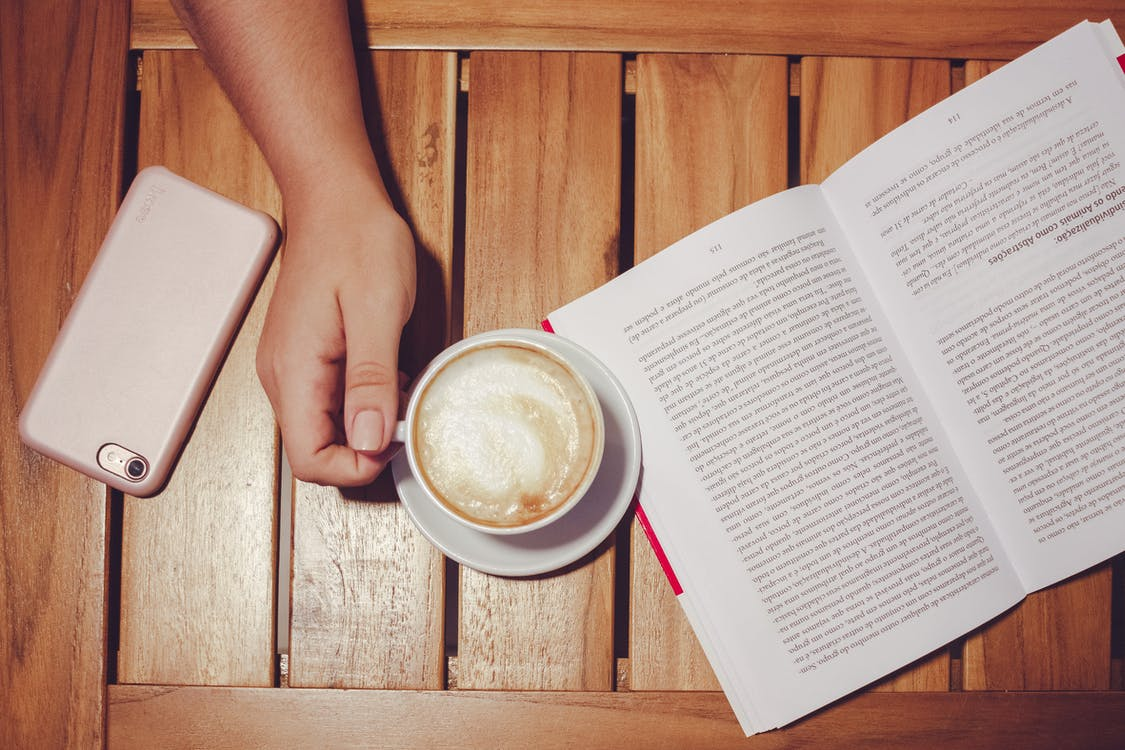 Person's Hand Holding White Coffee Mug With Plate on Brown Wooden Board With White and Black Book