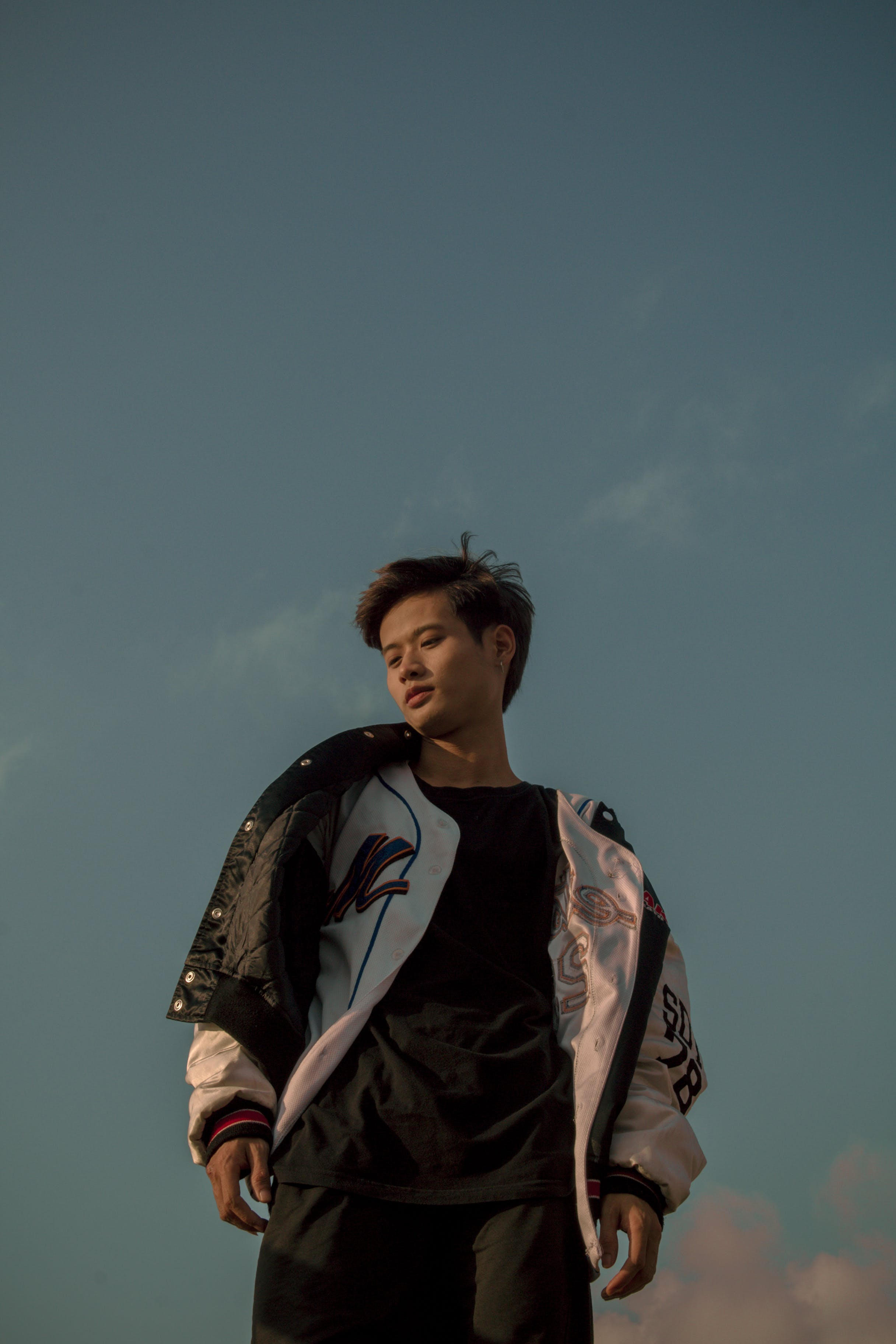 Man in White Jacket Standing Under Blue Skies