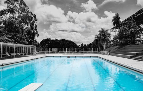 White Concrete Framed Swimming Pool Near Benches With Gate Surrounded by Trees