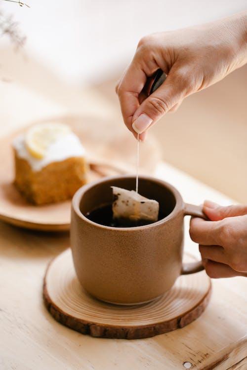 Person Pouring Black Liquid on Brown Ceramic Mug