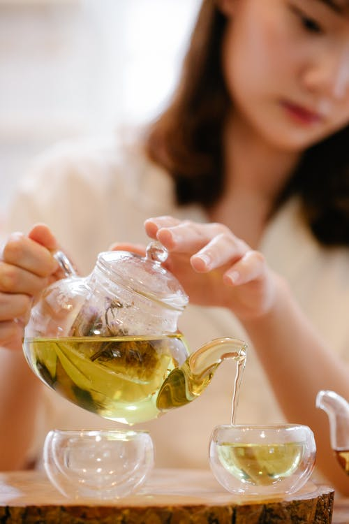 Woman Holding Clear Glass Teapot