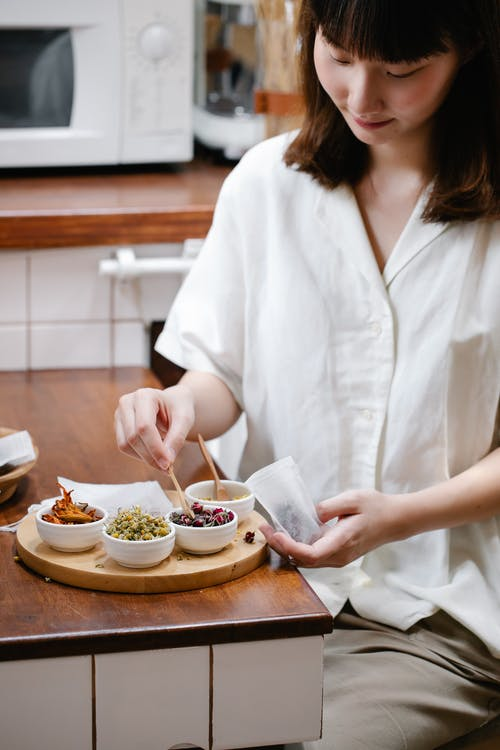Woman in White Button Up Shirt Holding White Ceramic Bowl With Food