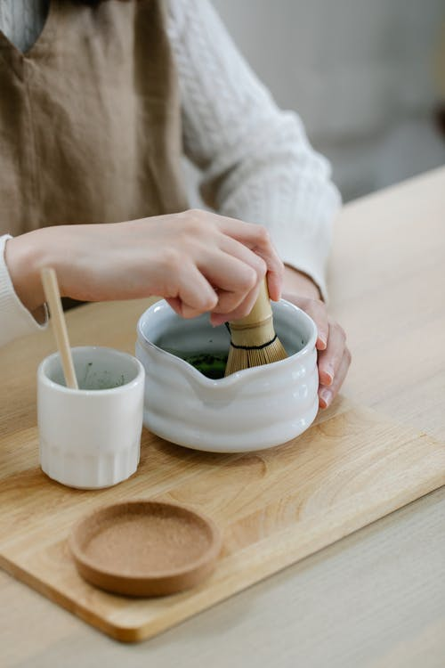 Person Holding White Ceramic Bowl With Green Powder